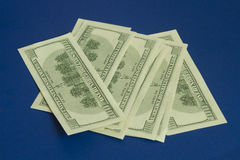 100 долларовых банкнот на синей предпосылке Стоковая Фотография