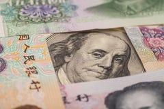 100 долларовых банкнот окруженных китайскими юанями Стоковое Изображение