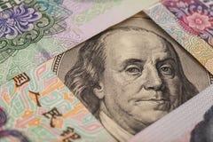 100 долларовых банкнот окруженных китайскими юанями Стоковое Изображение RF