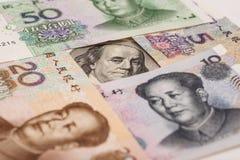 100 долларовых банкнот окруженных китайскими юанями Стоковые Фото
