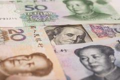 100 долларовых банкнот окруженных китайскими юанями Стоковое фото RF