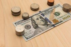 100 долларовых банкнот окруженных стогом монеток Стоковые Фото