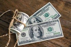 100 долларовых банкнот свернутых вверх с веревочкой Стоковые Фотографии RF