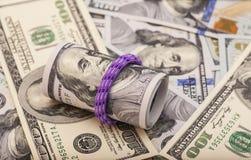 100 долларовых банкнот свернутых вверх с rubberband на долларах Стоковое Изображение RF