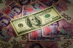100 долларов банкноты на предпосылке украинского hryv Стоковое фото RF