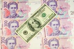 100 долларов банкноты на предпосылке украинского hryv Стоковое Изображение RF