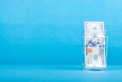 100 долларов в стеклянном опарнике на правильной позиции, взгляд со стороны, Стоковые Фото