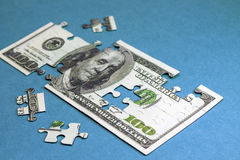 100 долларов в форме головоломки Концепция Стоковое Изображение RF