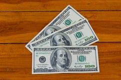 100 долларов на деревянной предпосылке Стоковые Фото
