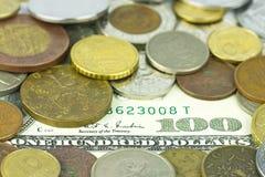 100 долларов под монетками Стоковое Фото