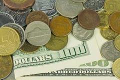 100 долларов под монетками Стоковая Фотография