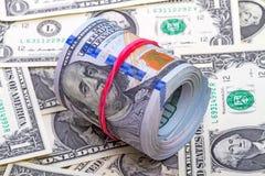 100 долларов свертывает вверх с красной резиной Стоковое Изображение