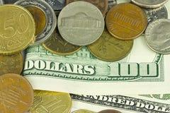 100 долларов с различными монетками закрывают вверх по предпосылке Стоковые Изображения