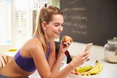 Одежда спортзала женщины нося смотря мобильный телефон Стоковые Изображения