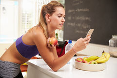 Одежда спортзала женщины нося смотря мобильный телефон Стоковые Изображения RF