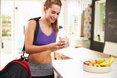 Одежда спортзала женщины нося смотря мобильный телефон Стоковые Фото