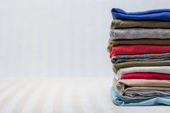 Одежда сложенных людей на stripy предпосылке Стоковая Фотография RF