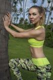 Одежда тренировки детенышей довольно белокурая счастливая женская нося протягивая склонность против пальмы во время красивого лет Стоковое фото RF