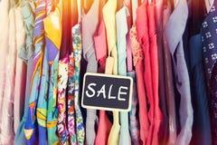 Одежды вися на шкафе в магазине Стоковое фото RF