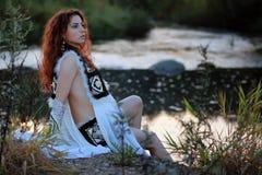 Одежды девушки сидят фантазия реки стоковая фотография rf