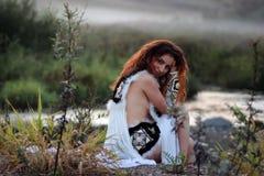 Одежды девушки сидят фантазия реки стоковые изображения