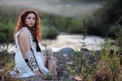 Одежды девушки сидят фантазия реки стоковое изображение