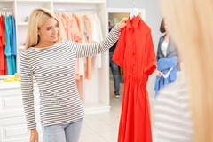 Одежды жизнерадостной молодой женщины покупая в бутике Стоковые Изображения