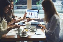 Одежды дизайнеров девушек работая совместно на магазине сети через портативный компьютер с насмешкой вверх по экрану и wifi Стоковые Изображения