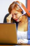 Одежды и шлемофон офиса молодой привлекательной женщины нося сидя столом смотря экран компьютера, работая с Стоковое фото RF