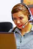 Одежды и шлемофон офиса молодой привлекательной женщины нося сидя столом смотря экран компьютера, работая с Стоковые Фотографии RF