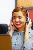 Одежды и шлемофон офиса молодой привлекательной женщины нося сидя столом смотря экран компьютера, работая с Стоковое Изображение RF