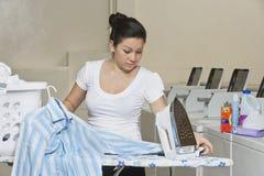 Одежды молодого женского работника утюжа в Laundromat стоковое фото rf