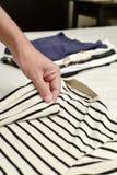 Одежды молодого человека складывая Стоковые Фото