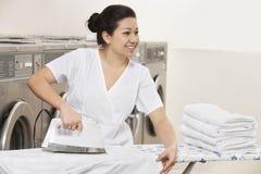 Одежды счастливого молодого работника утюжа пока смотрящ прочь в Laundromat стоковое изображение
