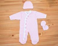 Одежды для newborn девушки на деревянной предпосылке Стоковая Фотография RF