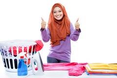 Одежды hijab молодой женщины нося утюжа и давать 2 большого пальца руки Стоковая Фотография RF