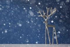 Олени сувенира серебряные на голубой предпосылке в снеге Стоковые Изображения