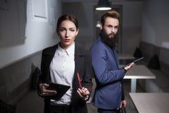 Одетый в костюмах бизнес-леди и человеке держите таблетки; Стоковые Изображения RF