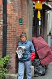Уборщик улицы читает газету Шанхай Китай стоковые фотографии rf