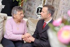 Одетый человек держа даму пожилых людей рук Стоковые Изображения RF