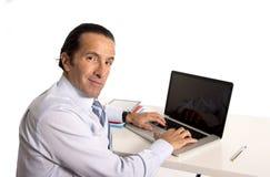 40 до 50 лет старого старшего бизнесмена работая на компьютере на столе офиса смотря уверенно и расслабленный Стоковая Фотография