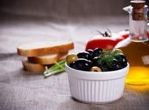 Оливки в белом шаре и малой бутылке оливкового масла на ткани джута Стоковое Изображение