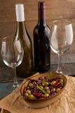 Оливки, который служат в контейнере бутылки вина Стоковая Фотография