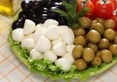 Оливки моццареллы, черных и зеленых, томаты вишни на зеленом цвете Стоковые Фотографии RF
