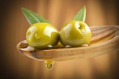 Оливки с маслом падения на деревянной ложке Стоковые Изображения RF
