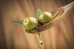 Оливки с маслом падения на деревянной ложке Стоковая Фотография RF