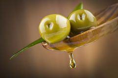 Оливки с маслом падения на деревянной ложке Стоковое Фото