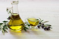 Оливковое масло и ветви оливок на белой деревянной предпосылке Стоковые Изображения