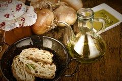 Оливковое масло, хлеб, луки и законсервированные томаты Стоковая Фотография