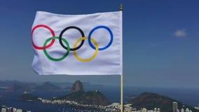 Олимпийский флаг развевая на горизонте Рио-де-Жанейро обозревает сток-видео